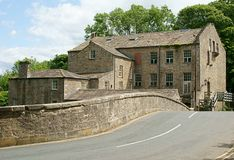 Old Mill on Country Road. An old cotton / flour mill in North Yorkshire, England UK, sited near a road bridge Stock Image