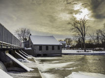 Old Mill at the dam in winter. Frozen river waterfall Royalty Free Stock Images