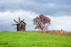 Old mill on the hillock. Old wind mill and the tree on the hillock stock photo