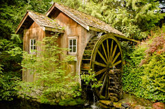 Old Mill on Stream. Old wooden mill with water wheel on stream among trees Royalty Free Stock Images