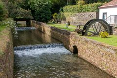 Old mill with a stream enclosed in a stone channel with brickwork royalty free stock image