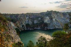 Old mine become lake. Rock mountain and emerald color of lake occur from abandon mine in Thailand Royalty Free Stock Photo