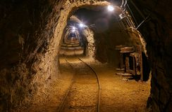 Old Mine Tunnel. Mining tunnel with lights and rails Royalty Free Stock Photos