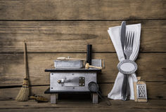 Old miniature of an oven with cutlery on an ancient rustic backg Stock Images