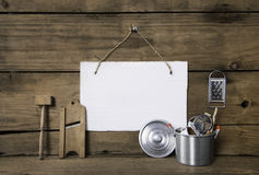 Old miniatures of kitchenware with a white placard on an old woo Stock Photography
