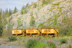 Old mining buggies on tracks left to rust at an outdoor museum in yellowknife Royalty Free Stock Photography