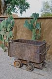 Old Mining Ore Cart. An old mining ore cart sits in front of a huge prickly pear cactus and against an adobe wall stock photo