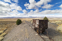 Old mining ore cart on tracks underneath a beautiful blue sky. With clouds in the Nevada desert at the Berlin Ghost Town Royalty Free Stock Photos