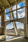 Old mining tower in remodeling with large windows looking at an intense blue sky. With white clouds on a splendid sunny day in Maasmechelen Belgium royalty free stock photography