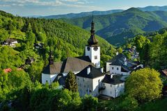 Old mining village. Spring in Slovakia. Old mining village. Historic church in Spania dolina. Springtime colored trees at sunset Royalty Free Stock Image