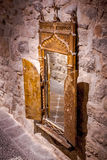 Old mirror with golden frame. Photograph of an ancient mirror on the stone wall royalty free stock images