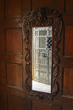 Old mirror. Photo shows an old mirror having a wooden frame. The frame is carved. At the top, there is an image of the human head above the door frame. It is stock photography