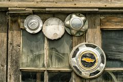 Old mixed hubcaps in a  window stock photos
