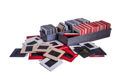 Old 35 mm mounted film slides and plastic boxes. 35 mm mounted film slides into the plastic and cardboard different colored frames and plastic boxes isolated on Royalty Free Stock Image