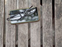 Old mobile handy telephone touchscreen and reading glasses Stock Photos
