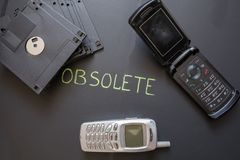 Old mobile phones and floppy disks on dark background. stock photography