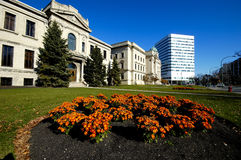 Old and Modern. Old government buildings set back from a fancy lawn with a modern skyscraper in the background Royalty Free Stock Image