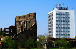 Old and modern. Two buildings: an old ruin and a modern office block. Time, progress, diversity Stock Photos