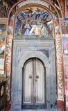 Old monastery door bible murals. Old monastery door with bible scene mural around it Royalty Free Stock Photography