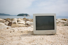 Old monitor on the rocky beach. Royalty Free Stock Photos