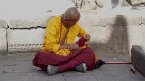 The Monk Prepares for Prayer. The Old Monk Prepares for Prayer Near the Buddhist Temple. Nepal stock video footage