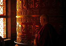 Old Monk Rotating a Prayer Wheel Stock Image