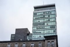 Modern office tower and older stone house in Old Montreal Vieux Montreal, Quebec. royalty free stock photography