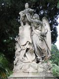 Old monument, brooding angel on a pedestal with flowers and a sea anchor. Monument in one of the parks of Cagliari, Sardinia, Italy stock images