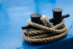 Old mooring bollard with heavy ropes. A closeup Stock Image