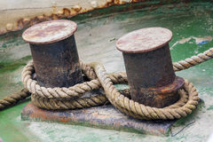 Old mooring bollard with heavy ropes Stock Image