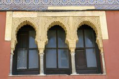 Three arched windows in Arabic style. Old Moorish house in the city of Cordoba, Spain. Yellow stone arches and columns. Red wall of the building. Arabian mosaics Stock Images