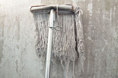 Old mop. Wood flooring is considered old. It also puts forward the old white wall Stock Photography