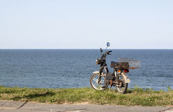 Old moped. Old rusty moped at the edge of the sea Stock Photography