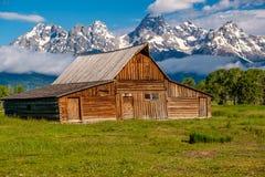 Old barn in Grand Teton Mountains. Old mormon barn in Grand Teton Mountains with low clouds. Grand Teton National Park, Wyoming, USA Stock Photos