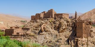 Old Moroccan clay kasbah perched on hill in Atlas mountains, Morocco, North Africa royalty free stock photos