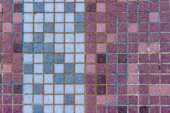 Old mosaic tiles of different colors lined verticaly Stock Photo