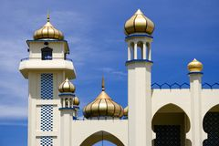 Old mosque in Malaysia. Old white mosque in Malaysia with turrets, towers and golden domes Royalty Free Stock Photo