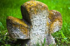Old moss-grown stone cross. With engraved Old Church Slavonic inscriptions. Kyiv, Ukraine. Close up Stock Image