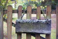 Old mossy signboard with chain on a wooden fence Stock Image