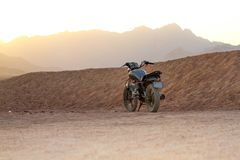 Vintage grey motorcycle in the desert at sunset. Old moterbike among sand dunes, in the arid western desert of Egypt. Used by the leader of a desert safari stock images