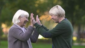 Old mother and adult daughter giving high-five, celebrating life, family love