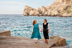 Old mother and adult daughter in retro old-fashioned clothes holding hands walking and talking on the stone beach of the blue sea Royalty Free Stock Photos