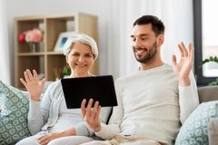 Old mother and adult son with tablet pc at home stock image