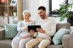 Old mother and adult son with tablet pc at home royalty free stock image