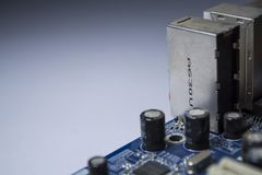 The old motherboard from the PC. Blue color. Dust. Repair of the computer. Modern technologies. Workshop. stock image