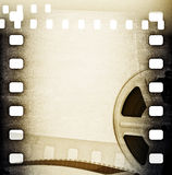 Old motion picture film reel with film strip. Vintage background. Old motion picture film reel with film strip Royalty Free Stock Images