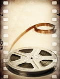 Old motion picture reel with film strip. Vintage background. Old motion picture film reel with film strip. Vintage background Royalty Free Stock Photography