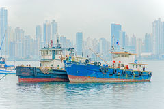 Old motor boats and panama skyscrapers on the background. Stock Photography