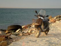 Old motor scooter on the rocky shore of the broad sea Bay in the evening in the warm glow of the setting sun. Large boulders on the beach. An old scooter is stock photos