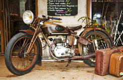 Old motorbike. An old motorbike outside a restaurant with 2 suitcases beside it Royalty Free Stock Photo